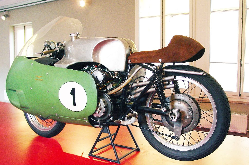 The rear 3/4 view of the silver-and-green 1955 Moto Guzzi V8 racer