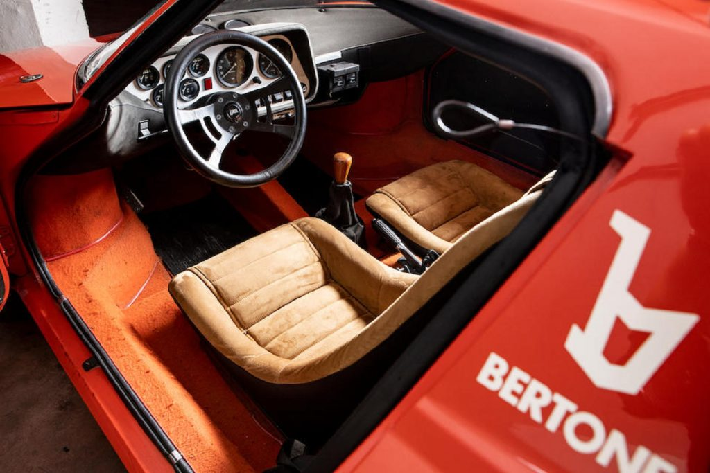 The tan-leather seats and the dashboard of a red 1974 Lancia Stratos HF Stradale