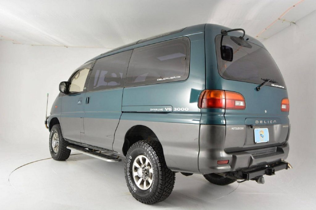 The rear 3/4 view of a turquoise 1994 Mitsubishi Delica Space Gear LWB 4x4