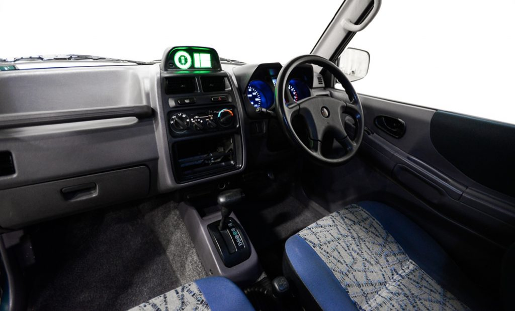 The gray dashboard and blue-and-silver front seats of a 1995 Mitsubishi Pajero Mini VR-II