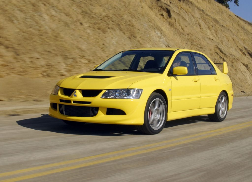A yellow 2003 Mitsubishi Lancer Evolution VIII on a canyon road