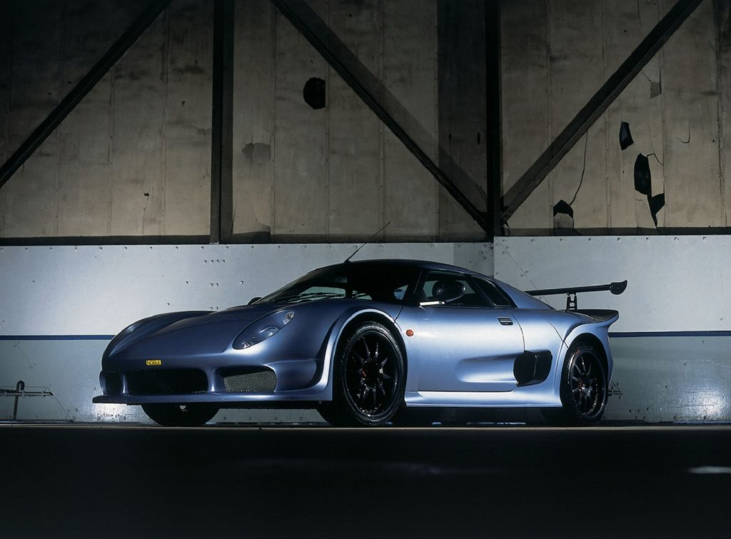 A silver 2004 Noble M400 in a dark warehouse