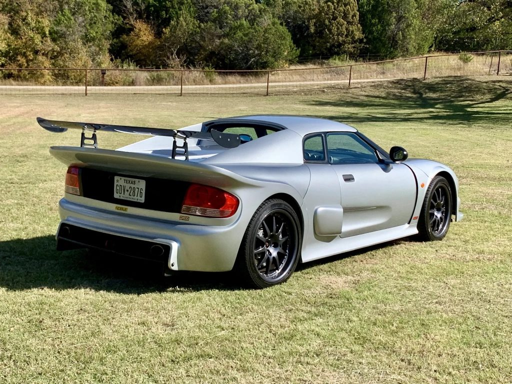 The rear 3/4 view of a silver 2005 Noble M400 in a grassy field