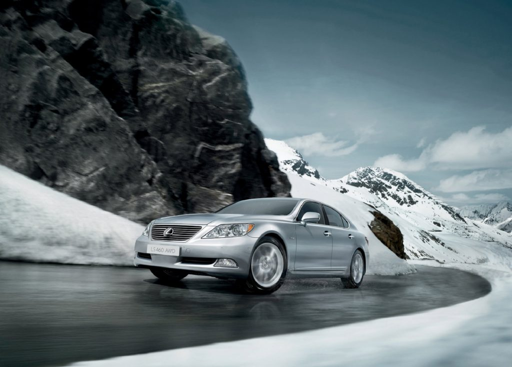 A silver 2009 Lexus LS 460 AWD drives up a wet snowy mountain road