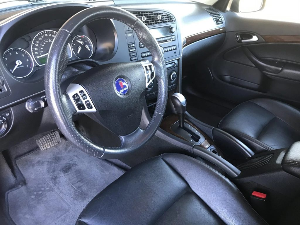 The black dashboard and black-leather front seats of a 2009 Saab 9-3 SportCombi 2.0T