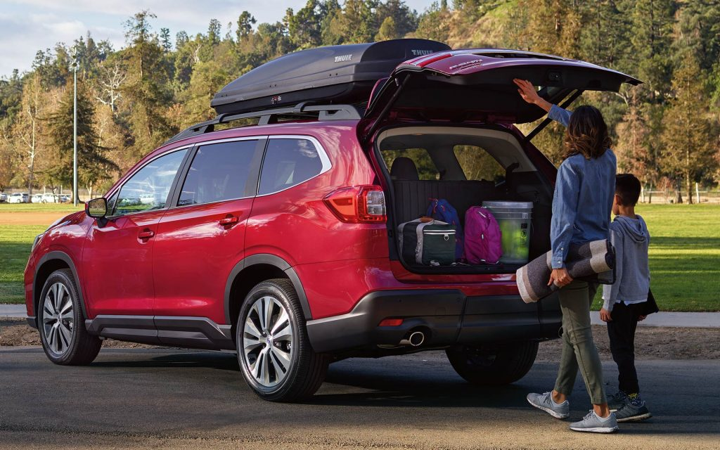 A woman and a child loading luggage in the trunk of a red Subaru Ascent.