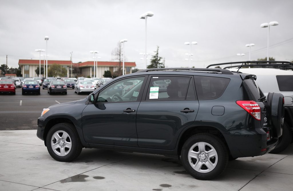 A blue 2012 Toyota RAV4 parked on display at a dealership lot