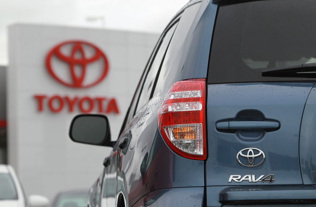 A look at the rear of a blue 2012 Toyota RAV4 with the red Toyota logo in the background