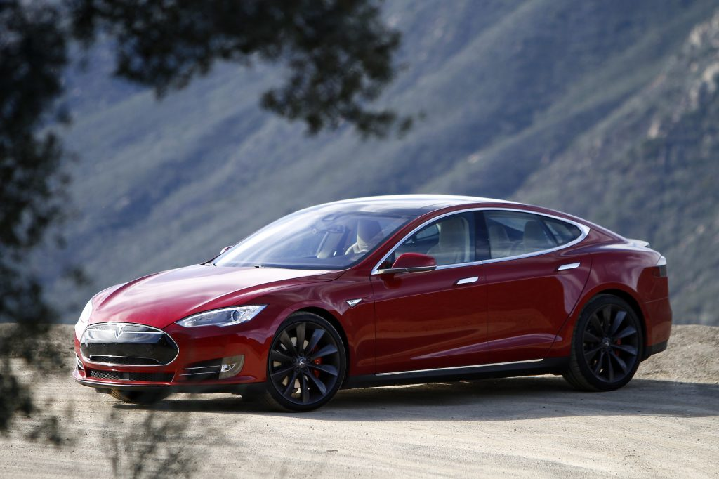 A red A 2015 Tesla Model parked on a dirt road in front of mountains in California S P85D