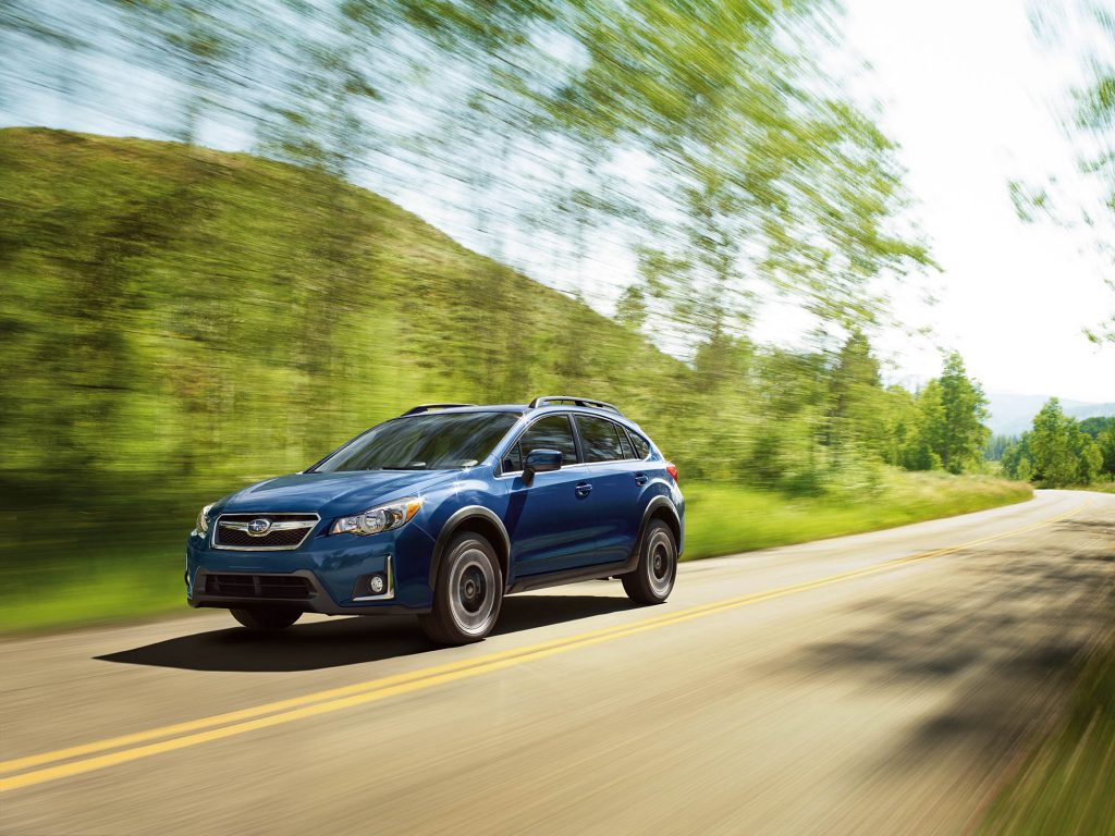 A blue 2016 Subaru Crosstrek driving down a highway road
