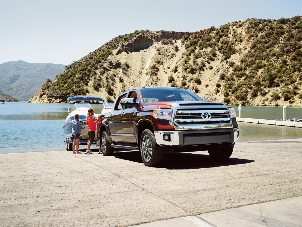 Two children stand next to a maroon 2016 Toyota Tundra towing a boat on a boat ramp overlooking a lake and mountains