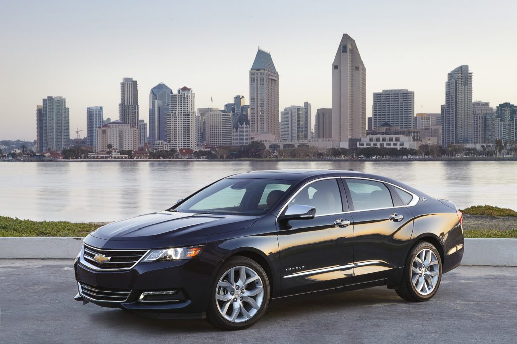 A black 2018 Chevy Impala parked in front the river with the city skyline in the background