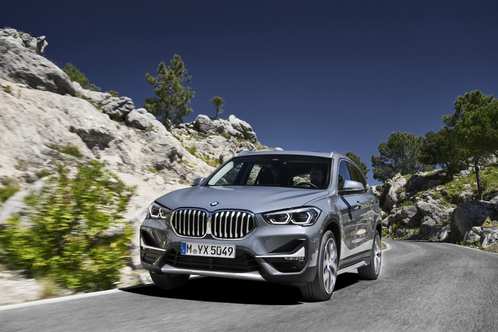 A silver 2020 BMW X1 European model travels on a paved road on a rocky hill
