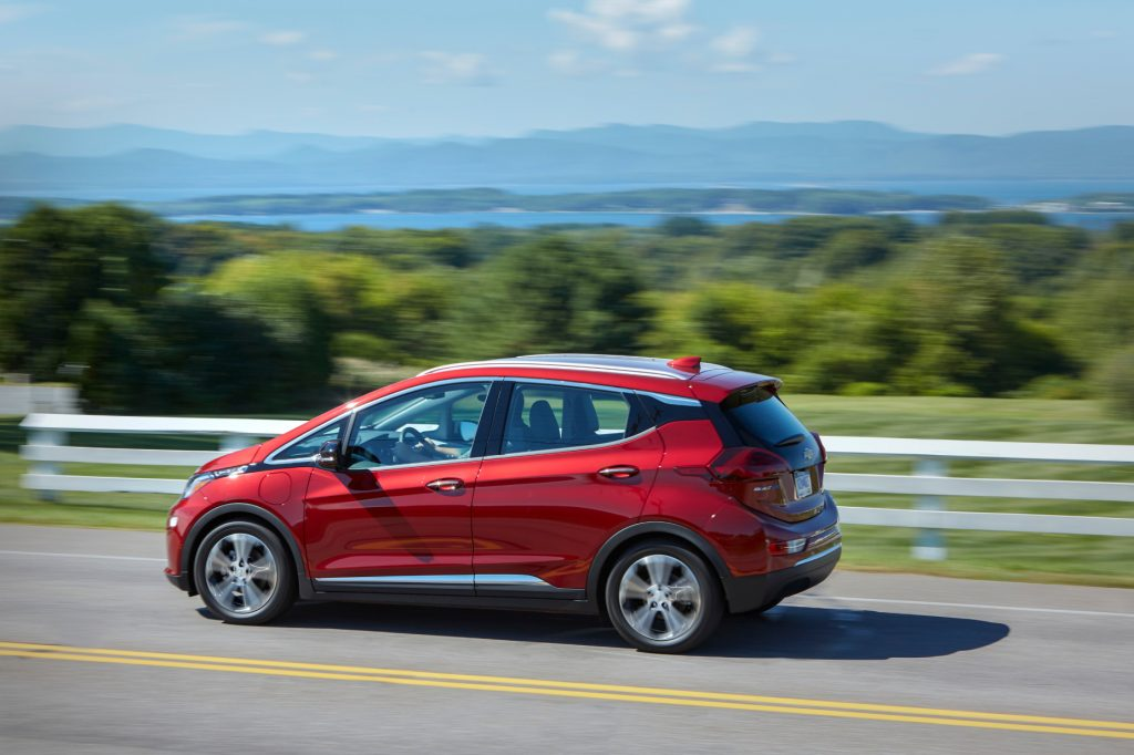 A red 2020 Chevy Bolt EV driving down a country road
