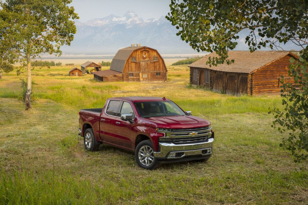 A red 2020 Chevy Silverado LTZ parked in a field with trees in the background