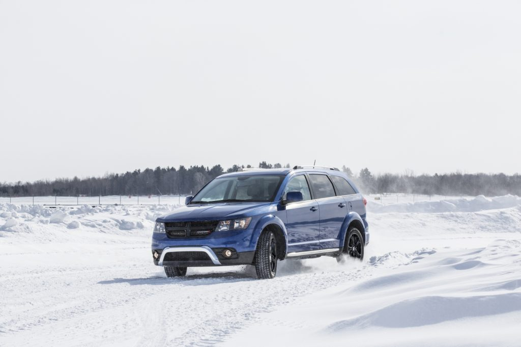 A blue 2020 Dodge Journey driving through snow