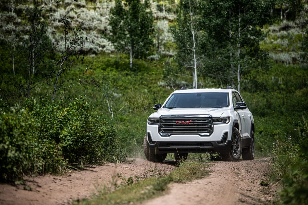 A white 2020 GMC Acadia AT4 parked on a dirt trail