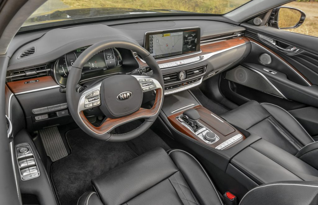 A close-up look at the interior of the 2020 Kia K900 with leather seats and wood trim