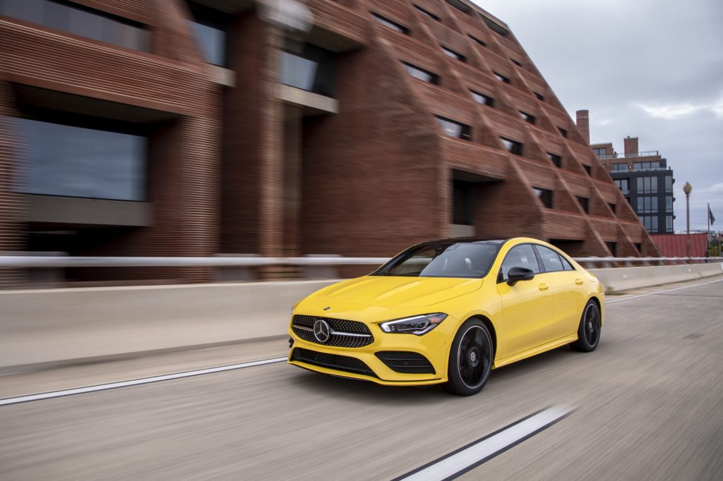 A yellow 2020 Mercedes-Benz CLA 250 4MATIC driving down a city road next to a building