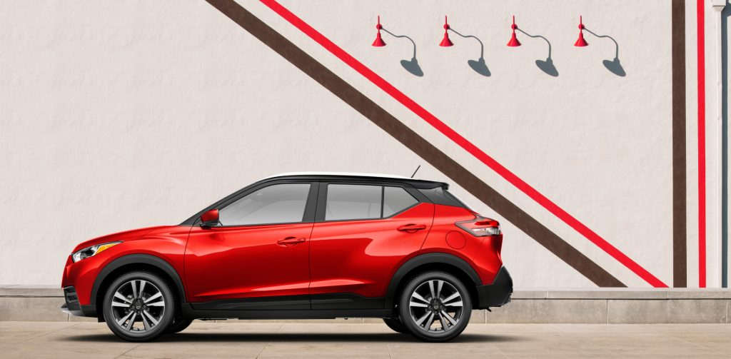 A red 2020 Nissan Kicks parked next to an artsy wall