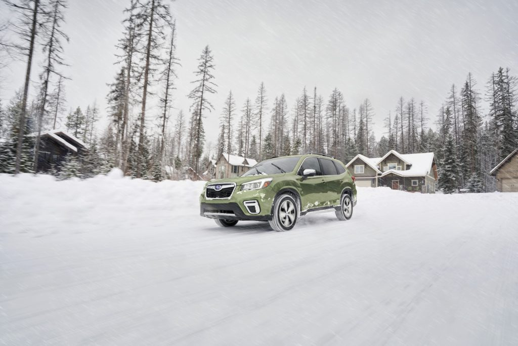 A green 2020 Subaru Forester driving through a snowy road