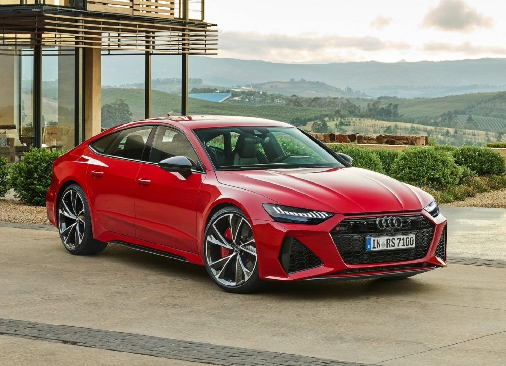 A red 2021 Audi RS7 overlooking a forest mountain