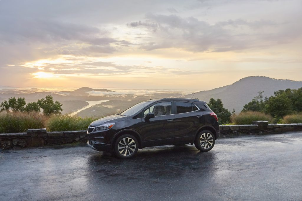 A black 2021 Buick Encore on display in front of mountain range