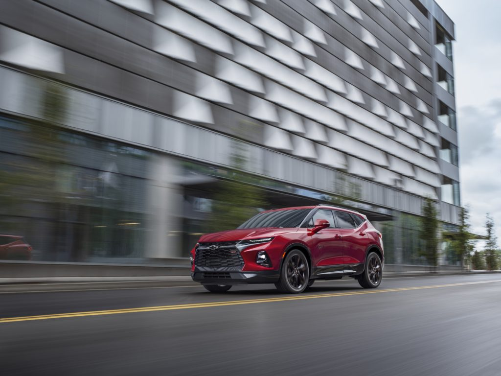 A red 2021 Chevrolet Blazer family SUV safely driving down a city road