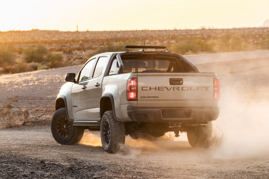 A silver 2021 Chevrolet Colorado ZR2 kicks up some dust on a dirt road
