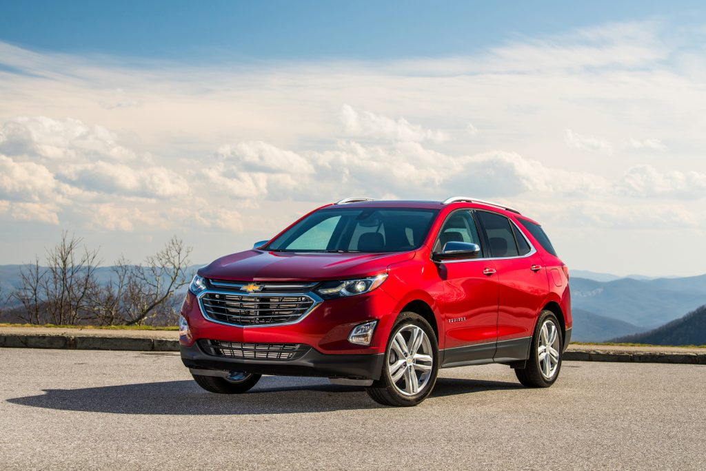 A red 2021 Chevy Equinox parked on pavement with a blue sky in the background
