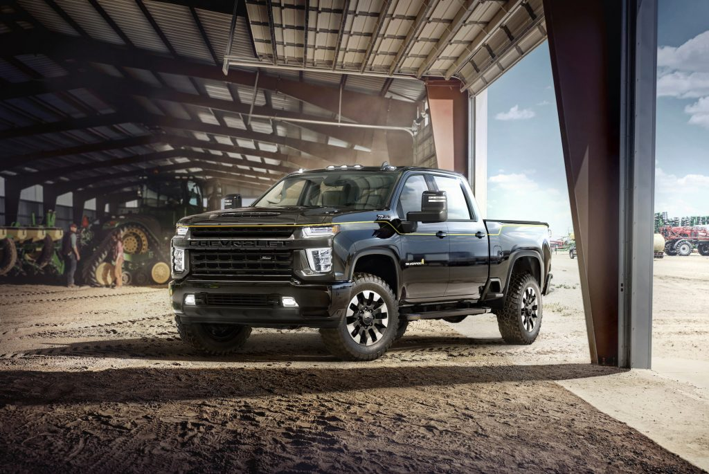 A black 2021 Chevy Silverado HD Carhartt Special Edition parked in a dusty barn with tractors