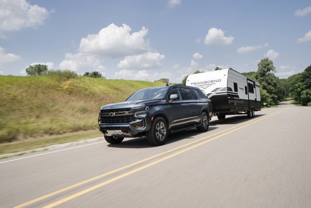 A black 2021 Chevy Suburban large SUV towing a white and blue RV on a highway road