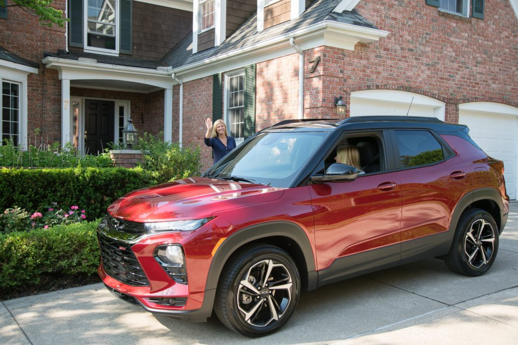 A red 2021 Chevy Trailblazer parked in a driveway in front of a house