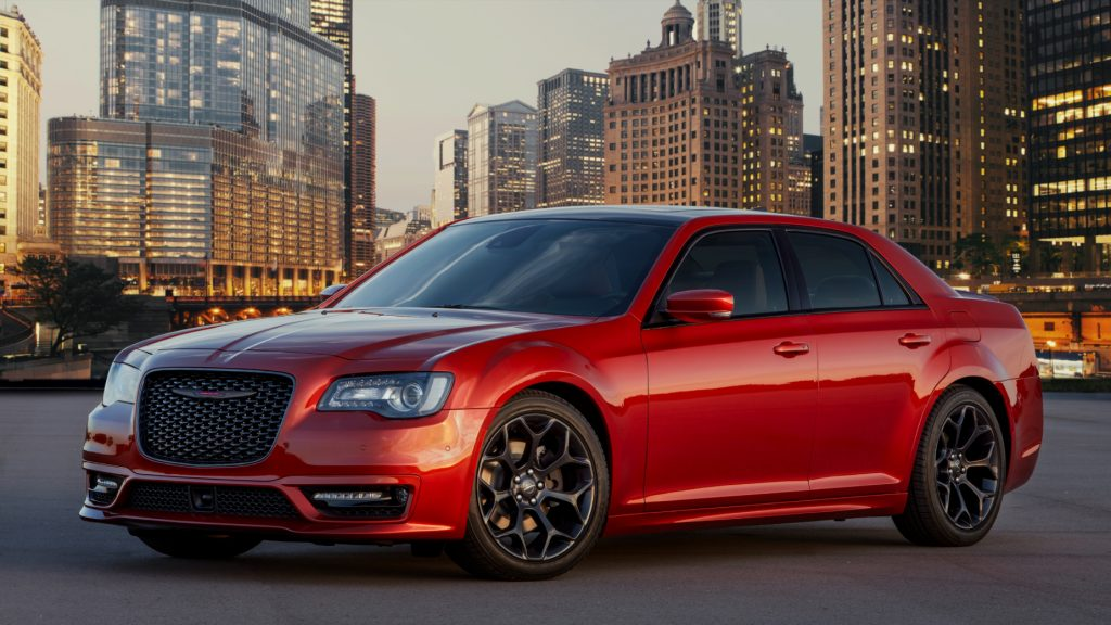 A red 2021 Chrysler 300 on display with a cityscape in the background