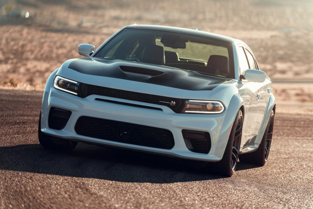 A white and black 2021 Dodge Charger driving on a track