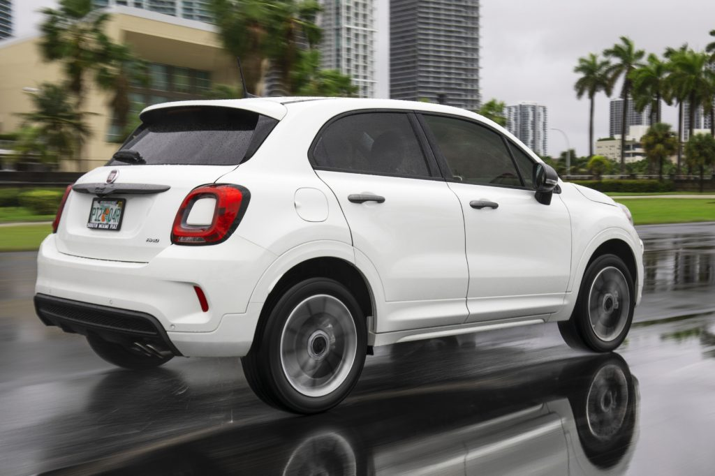 A white 2021 Fiat 500X subcompact SUV driving down a city road