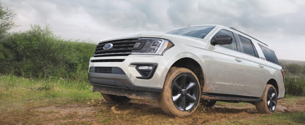 A white 2021 Ford Expedition large SUV driving over a dirt hill