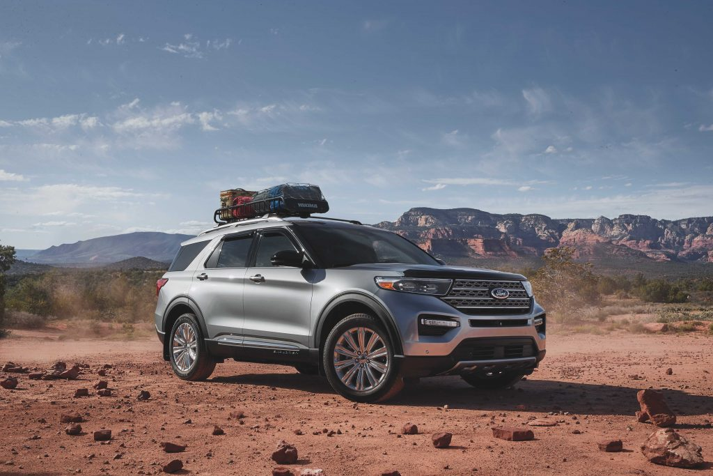 A silver 2021 Ford Explorer with a bag mounted on its roof rack driving down a dirt road