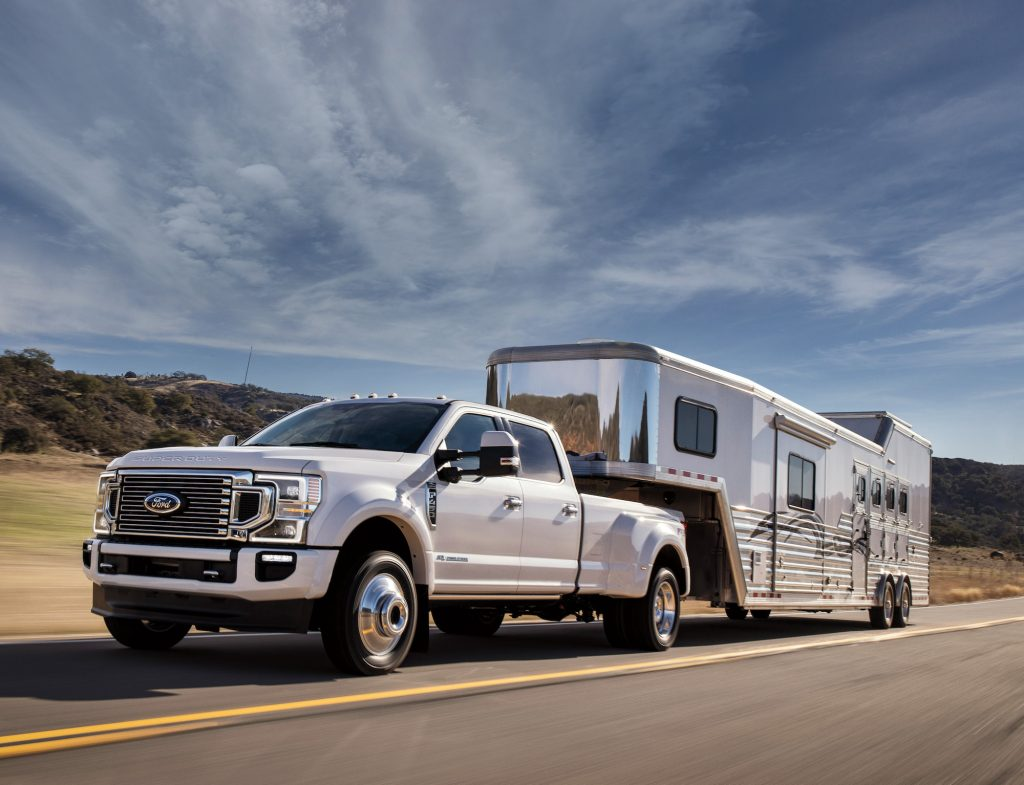 A Ford F-450 Crew Cab 4x4 in Star White Metallic Tinted Clearcoat with FX4 Off-Road Package and available equipment towing a large trailer on the highway