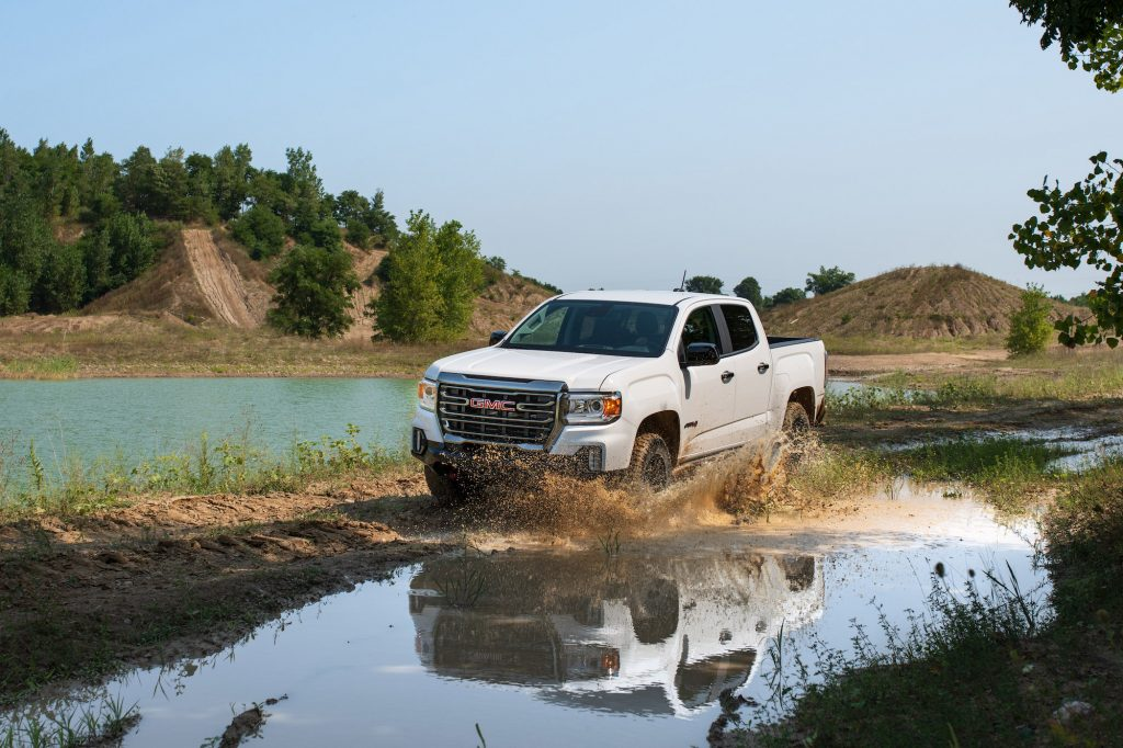 A white 2021 GMC Canyon AT4 Off-Road Performance Edition splashes through muddy water