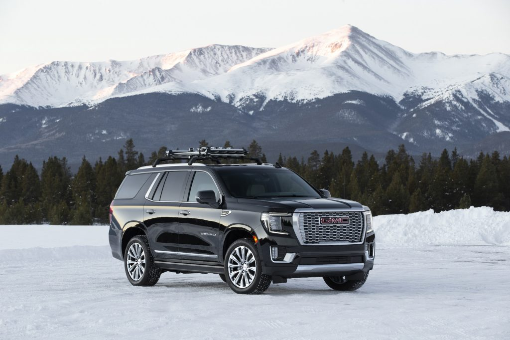 A black 2021 GMC Yukon Denali parked on snow in front of pine trees and snow-capped mountains