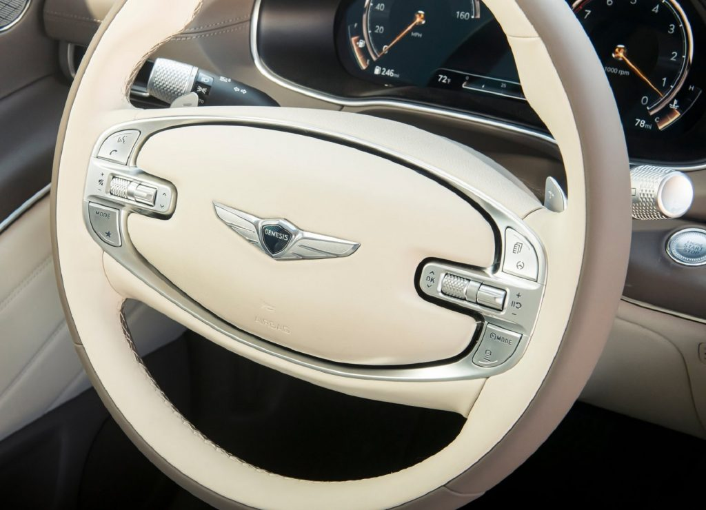 The 2021 Genesis GV80's white-and-brown 2-spoke steering wheel