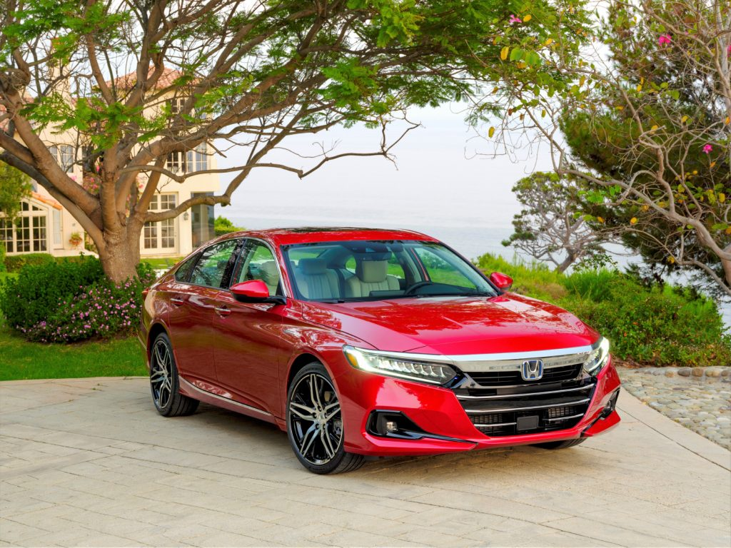 A red 2021 Honda Accord Hybrid parked in a driveway with a house and trees in the background