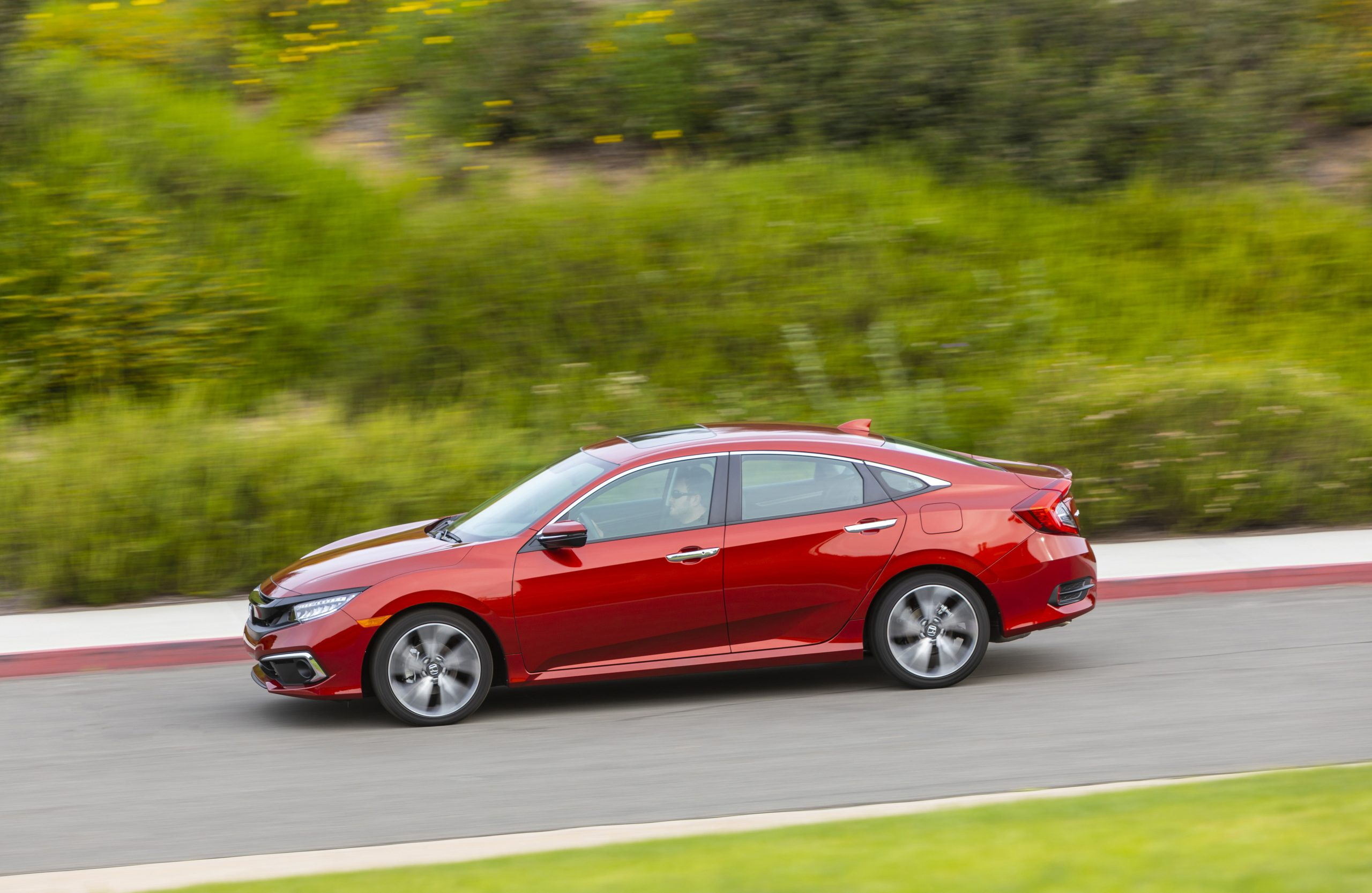 a red Honda Civic model driving at speed on a scenic country road