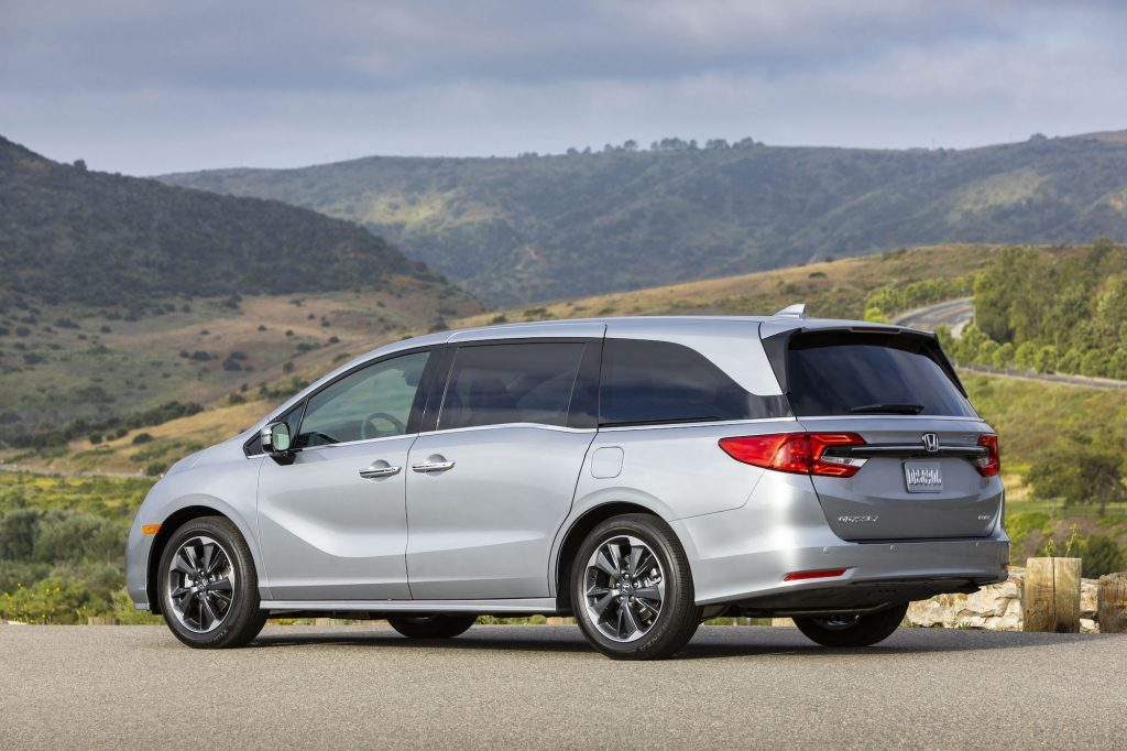 A silver 2021 Honda Odyssey parked on a road in front of mountains