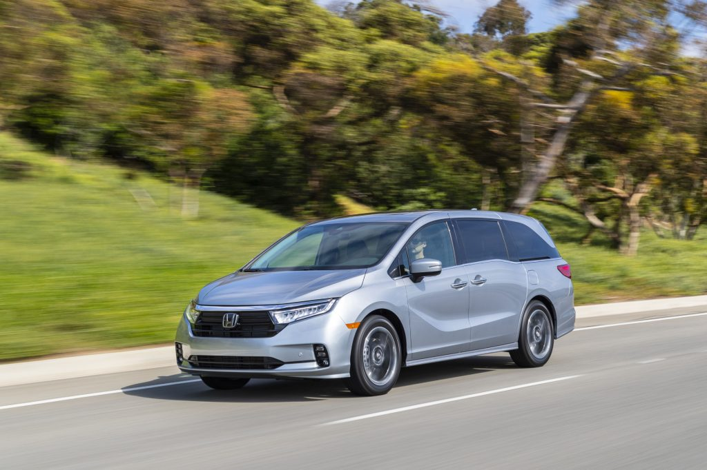 A silver 2021 Honda Odyssey driving down a highway road