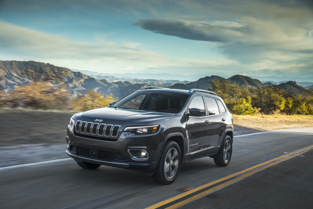 2021 Jeep® Cherokee Limited driving down a sunlit roadway