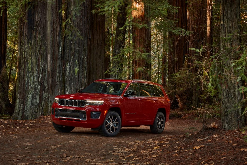 A red 2021 Jeep Grand Cherokee L Overland in a forest