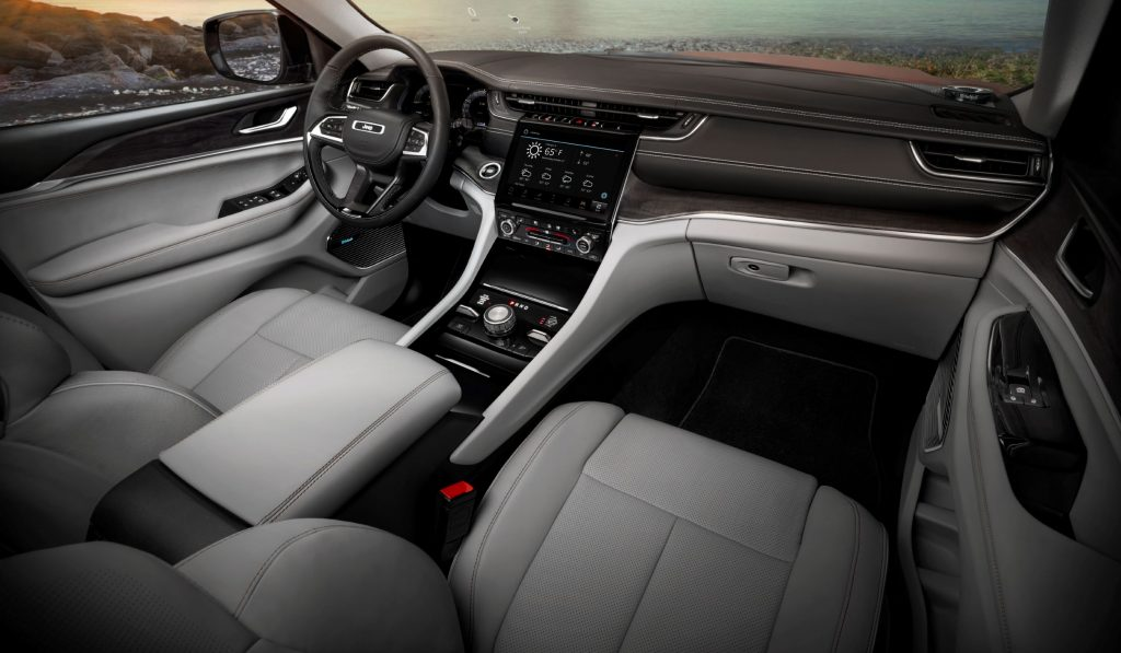 The white front seats and wood-trimmed dash of the 2021 Jeep Grand Cherokee L Overland