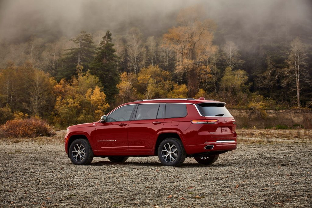 The rear 3/4 view of a red 2021 Jeep Grand Cherokee L Overland by a forest